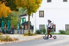 Weinig jong geitjejongen in helm het berijden met zijn autoped in de stad Royalty-vrije Stock Afbeeldingen