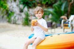 Weinig jong geitjejongen het drinken kokosnotensap op tropisch strand stock afbeeldingen