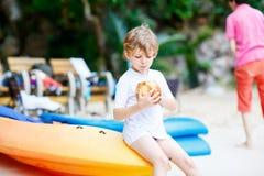 Weinig jong geitjejongen het drinken kokosnotensap op tropisch strand royalty-vrije stock foto