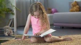 Weinig jong geitjelezing, die bij grappig verhaal in het boek van kinderen lachen, vroeg onderwijs stock video