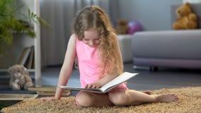 Weinig jong geitjelezing, die bij grappig verhaal in het boek van kinderen lachen, vroeg onderwijs royalty-vrije stock afbeelding