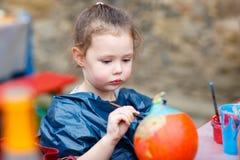 Weinig jong geitjemeisje die met kleuren op pompoen schilderen Stock Foto