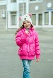 Weinig jong geitjemeisje pingelt binnen jasje lopend in de stad Het glimlachen chi royalty-vrije stock fotografie