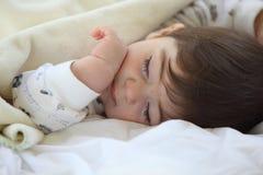 Weinig jong geitjeslaap op bed. Stock Foto