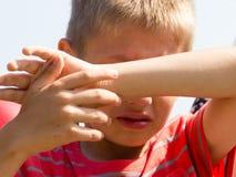 Weinig jong jongensjong geitje die ogen van zonlicht behandelen stock fotografie