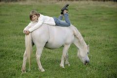 Weinig jong meisje in een witte sweater en jeans die op de rug van een witte poney liggen Levensstijlportret Royalty-vrije Stock Foto
