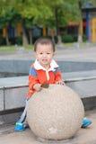 Weinig jongen achter de ronde steen Stock Fotografie