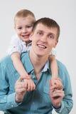 Weinig jongen achter gelukkige vaderomhelzingen Stock Afbeelding