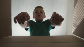 Weinig jongen bekijkt in doos met emoties en gevoel gezicht Kind het openen doos met gift en het trekken van handen om het te nem stock videobeelden