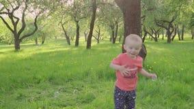 Weinig jongen bekijkt zeepbels in park door oudershand Langzaam-Mo stock videobeelden