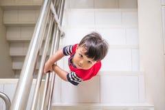 Weinig jongen beklimt direct hierboven op de treden van Royalty-vrije Stock Fotografie