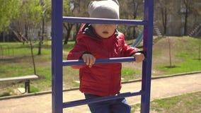 Weinig jongen beklimt ladder op speelplaats stock video