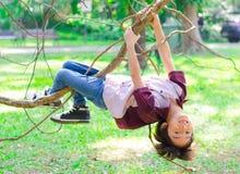 Weinig jongen beklimt op een boomrobe Stock Foto