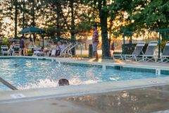 Weinig jongen bespat in zwembad terwijl de volwassenen in gazon CH zitten stock afbeelding