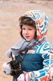 Weinig jongen bevindt zich op strand met verrekijkers in zijn handen en zoekt een te onderzoeken voorwerp Stock Foto