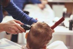 Weinig jongen bij de kapper Het kind is doen schrikken van kapsels haar royalty-vrije stock foto's