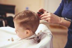 Weinig jongen bij de kapper Het kind is doen schrikken van kapsels haar stock fotografie