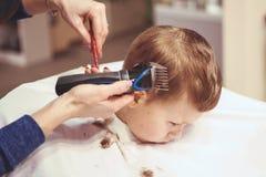 Weinig jongen bij de kapper Het kind is doen schrikken van kapsels haar stock foto