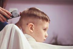 Weinig jongen bij de kapper Het kind is doen schrikken van kapsels haar stock afbeelding