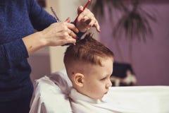 Weinig jongen bij de kapper Het kind is doen schrikken van kapsels haar royalty-vrije stock fotografie