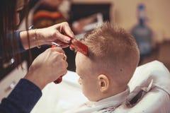 Weinig jongen bij de kapper Het kind is doen schrikken van kapsels haar royalty-vrije stock afbeeldingen