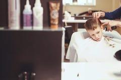 Weinig jongen bij de kapper Het kind is doen schrikken van kapsels haar stock afbeeldingen