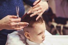 Weinig jongen bij de kapper Het kind is doen schrikken van kapsels haar stock foto's