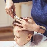 Weinig jongen bij de kapper Het kind is doen schrikken van kapsels haar royalty-vrije stock afbeelding