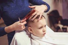 Weinig jongen bij de kapper Het kind is doen schrikken van kapsels haar royalty-vrije stock foto