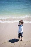 Weinig jongen bij de kust stock afbeelding