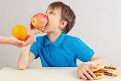 Weinig jongen bij de lijst kiest tussen fastfood en gezonde voeding op witte achtergrond stock foto's