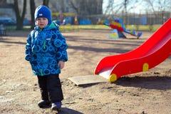 Weinig jongen bij een speelplaats stelt Stock Foto's