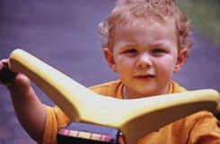 Weinig jongen bij het berijden van stuk speelgoed Stock Foto's