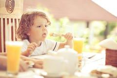 Weinig jongen bij ontbijt Stock Foto