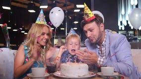 Weinig jongen blaast uit kaarsen op verjaardagscake stock footage