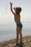 Weinig jongen in blauwe lafaards werpt omhoog steen Royalty-vrije Stock Fotografie