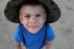 Weinig jongen in blauwe t-shirt en hoed stock foto