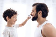 Weinig jongen borstelt tanden van de gebaarde mens met tandenborstel stock foto's