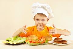 Weinig jongen in chef-kokhoed bij lijst met ingrediënten voor hamburger Royalty-vrije Stock Fotografie