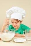 Weinig jongen in chef-kokhoed schuifelt deeg voor bakselcake Royalty-vrije Stock Foto's