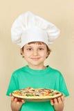 Weinig jongen in chef-kokshoed met gekookte eigengemaakte pizza Royalty-vrije Stock Foto's