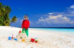 Weinig jongen de bouwzandkasteel op tropisch strand Stock Foto