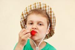 Weinig jongen in de de zomerhoed die verse aardbei eten Stock Foto's
