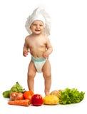 Weinig jongen in de hoed van de chef-kok onder verse groenten stock afbeeldingen