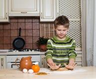 Weinig jongen in de keuken die het deeg voor koekjes voorbereiden die het rollen gebruiken. Stock Foto's