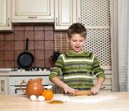 Weinig jongen in de keuken die het deeg voor koekjes voorbereiden die het rollen gebruiken. Royalty-vrije Stock Foto's