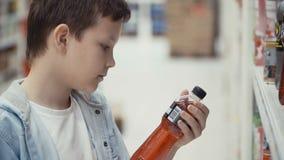 Weinig jongen in de supermarkt kiest een fles mineraalwater stock videobeelden