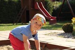 Weinig jongen in de zandbak Stock Afbeeldingen