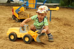 Weinig jongen in de zandbak Stock Foto