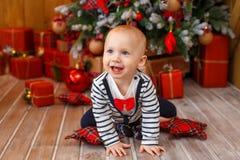 Weinig jongen dichtbij Kerstmisboom met giftdozen Stock Foto's